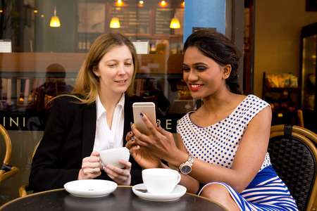 two ladies sitting outside a coffee shop looking at their phone Stok Fotoğraf