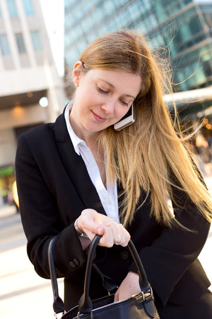 business woman on the phone and looking in her handbag photo