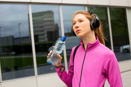 bottle with water: young woman thinking about going to the gym.