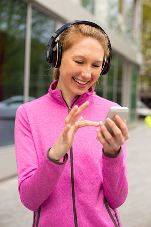 happy young woman wearing headphones and using her phone photo