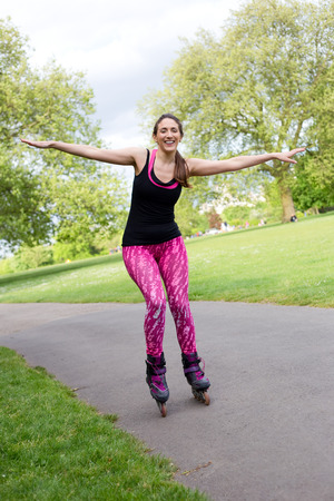 blading: happy woman balancing on her roller skates Stock Photo