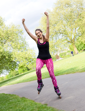 blading: happy young woman with roller skates in the park Stock Photo