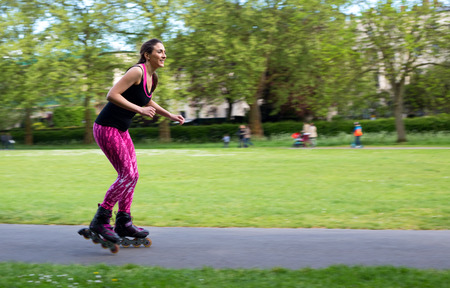 panning shot: panoramica di colpo di una giovane donna pattini a rotelle nel parco