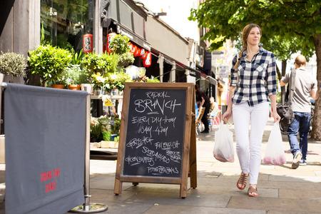 若い女性、彼女はショッピングを運ぶ 写真素材