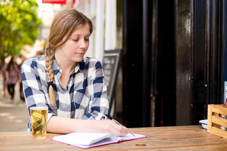 young woman writing in her diary and enjoying a drink. photo