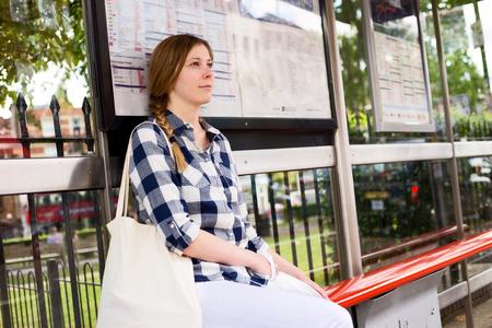 버스를 기다리는 젊은 여자