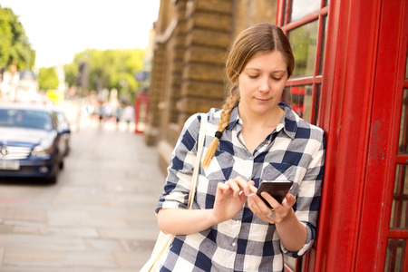 cell phone booth: young woman sending a text in london Stock Photo