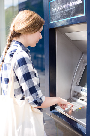 cashpoint: woman at the cash machine putting her pin in. Stock Photo