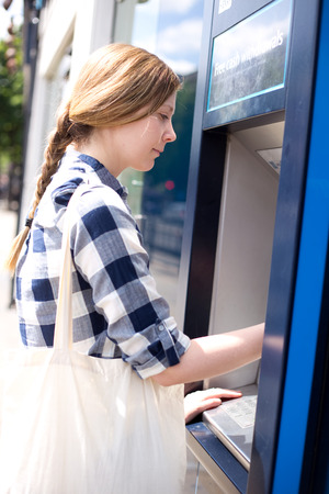 cashpoint: young woman at the atm machine.