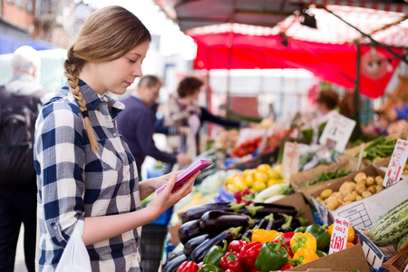 young woman reading her shopping list at the market photo
