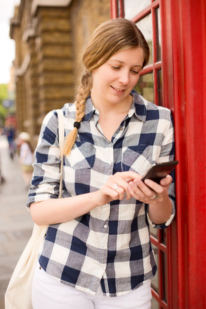 cell phone booth: young woman sending a text message in london
