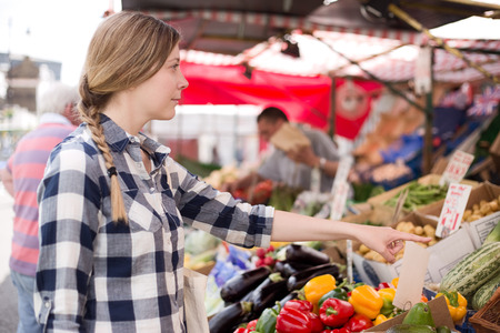 wants: young woman showing a market trader what she wants. Stock Photo