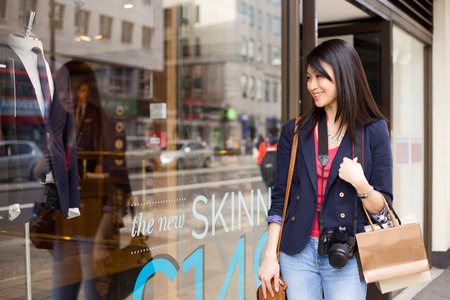 lifestyle shopping: young woman walking past the shops