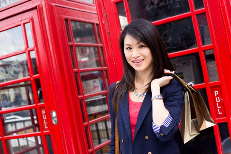 phonebooth: young chinese tourist with shopping bags in London