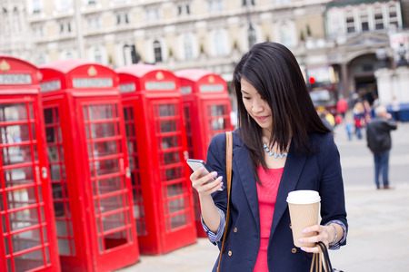 cabina telefonica: chinese girl in london checking her phone with a coffee