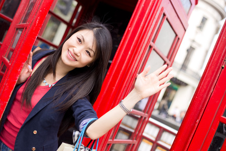 phonebox: young chinese girl waving from a london phonebox Stock Photo