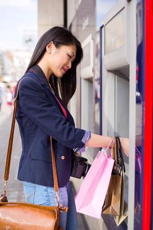 현금 점에서 돈을 인출하는 젊은 중국 여자