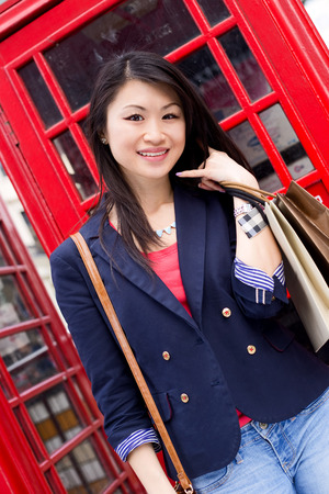 phonebooth: young chinese woman showing a call me symbol Stock Photo