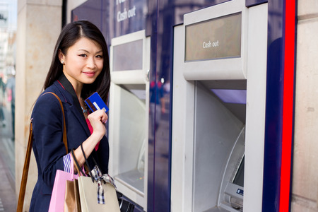 cashpoint: young chinese girl at the cashpoint
