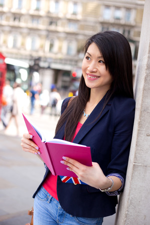young chinese woman holding her diary in the street. Stock Photo