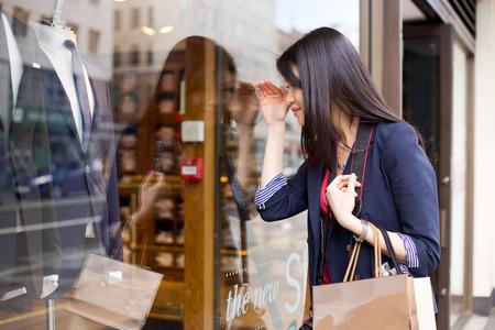 felicidade: Menina chinesa nova que olha em uma vitrine