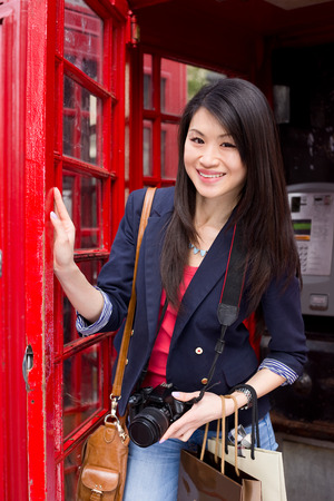 young chines tourist posing next to a London phonebox