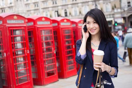 런던에서 전화로 젊은 중국 여자 스톡 콘텐츠