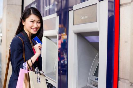 automatic transaction machine: niña china en el cajero automático