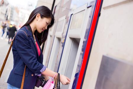 automatic transaction machine: joven china retirar dinero del cajero automático en Foto de archivo