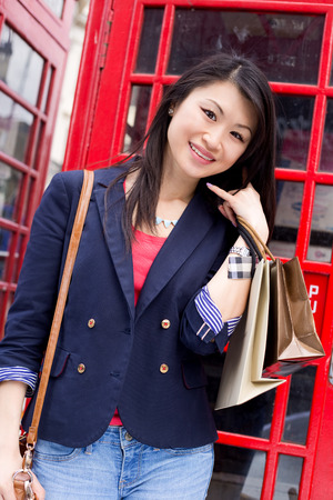 phonebox: young chinese girl showing a phone me symbol by a london phonebox