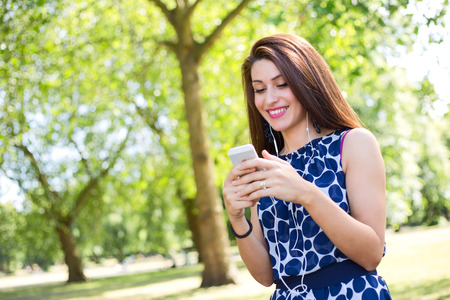 handsfree: young woman using her phone in the park