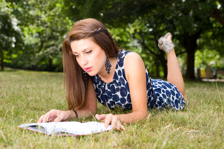 passtime: you woman reading a book in the park