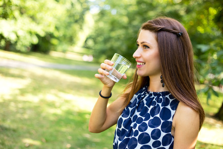 beber agua: Mujer joven que bebe un vaso de agua al aire libre