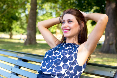 passtime: young woman relaxing on a bench in the park Stock Photo