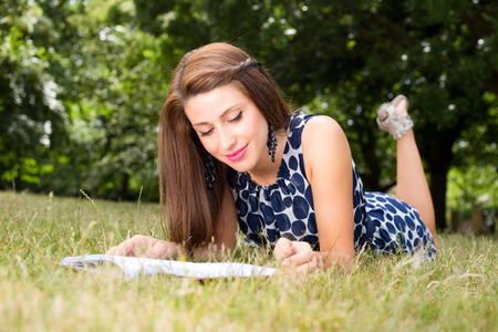 passtime: young woman reading a book in the park