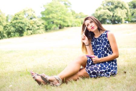 mujer pensando: mujer joven pensando en el parque que sostiene una pluma y el cuaderno Foto de archivo