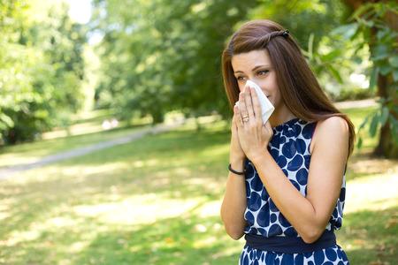 personne malade: jeune femme soufflant son nez dans le parc