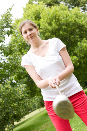 tee off: young woman holding a golf club preparing to tee off.