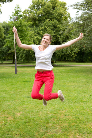 hole in one: young woman leaping with joy after a hole in one Stock Photo