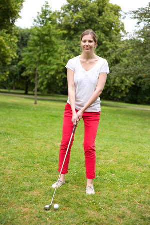 off course: young woman teeing off on the golf course Stock Photo