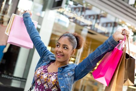 compras compulsivas: mujer feliz con bolsas de la compra en la calle