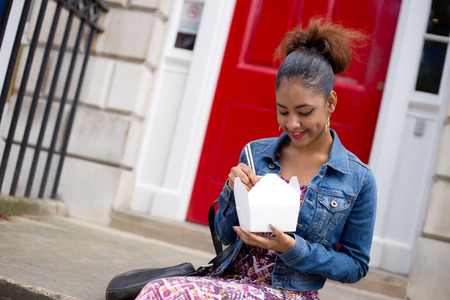 stoep: young woman eating a chinese take-away on her doorstep Stockfoto