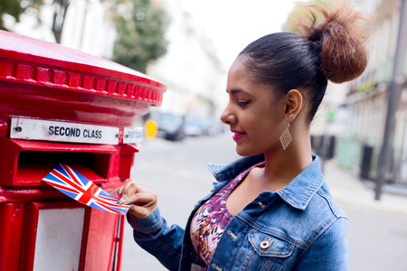 posting: young woman posting a postcard in London