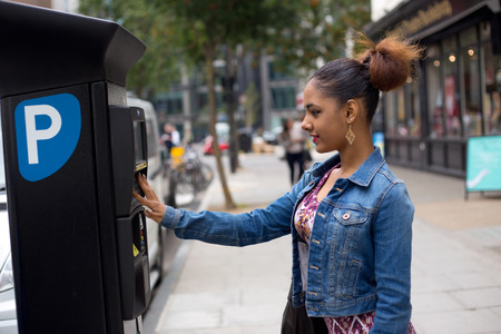 parking ticket: young woman paying her parking ticket Stock Photo