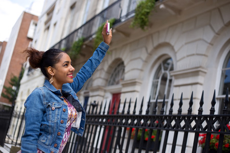 a young woman waving to her friends window from the street Stock Photo