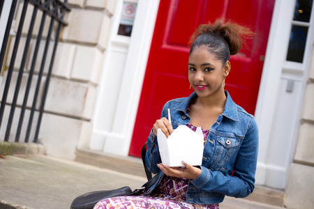 doorstep: young woman eating a chinese take-away on her doorstep Stock Photo