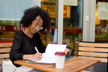young woman at a coffee shop writing in her diary Stock Photo