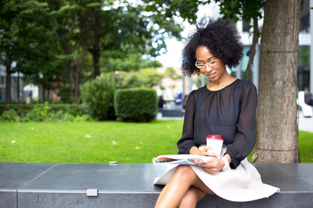コーヒーを飲みながら雑誌を読んで若い女性 写真素材