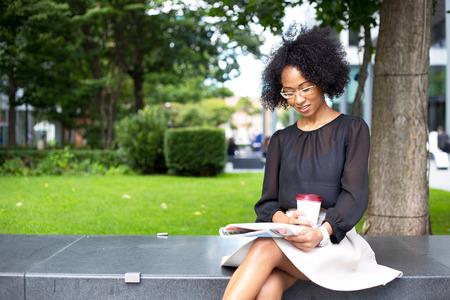jonge vrouw die een tijdschrift met een kopje koffie