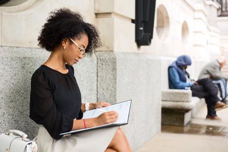 persona escribiendo: mujer de negocios joven escribiendo en su diario.